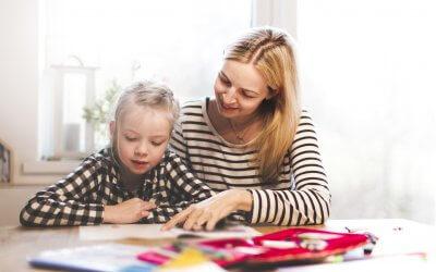 hermosa madre e hija juntas haciendo los deberes escolares en casa